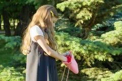 Niña rubia con el pelo rizado largo con un bolso de goma rosado en el parque La muchacha se abrió y las miradas en bolso fotografía de archivo libre de regalías