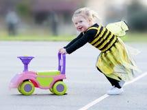 Niña rubia feliz en el traje de la abeja que empuja el juguete Imágenes de archivo libres de regalías