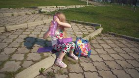 Niña rubia que come su almuerzo en parque el día soleado almacen de metraje de vídeo