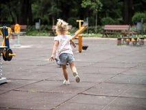 Niña rubia que corre en el patio Imagen de archivo libre de regalías