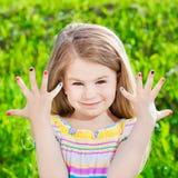 Niña rubia sonriente linda con la manicura mucho-coloreada Imagen de archivo libre de regalías