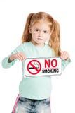 Niña seria con la muestra de no fumadores. Imagen de archivo