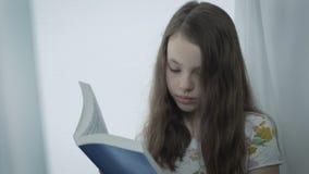 Niña seria hermosa que lee un libro por la ventana almacen de video