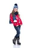 Niña sonriente bonita con el peinado rizado que lleva el suéter, la bufanda y el sombrero hechos punto con los patines aislados e Imagenes de archivo