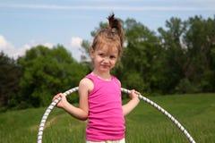 Niña sonriente con el aro de Hula que disfruta de día de primavera hermoso en el parque Fotografía de archivo