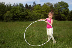 Niña sonriente con el aro de Hula que disfruta de día de primavera hermoso en el parque Foto de archivo