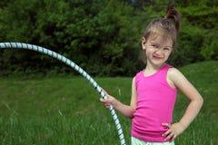 Niña sonriente con el aro de Hula que disfruta de día de primavera hermoso en el parque Imágenes de archivo libres de regalías