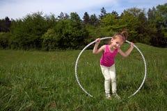 Niña sonriente con el aro de Hula que disfruta de día de primavera hermoso en el parque Fotos de archivo libres de regalías
