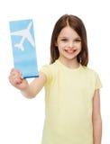 Niña sonriente con el billete de avión Fotografía de archivo