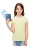 Niña sonriente con el boleto y el pasaporte Fotografía de archivo