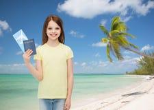 Niña sonriente con el boleto y el pasaporte Fotografía de archivo libre de regalías