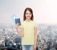 Niña sonriente con el boleto y el pasaporte Imágenes de archivo libres de regalías