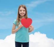 Niña sonriente con el corazón rojo Foto de archivo