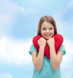 Niña sonriente con el corazón rojo Imagenes de archivo
