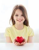 Niña sonriente con el corazón rojo en casa Imagenes de archivo