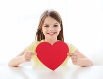 Niña sonriente con el corazón rojo en casa Foto de archivo libre de regalías