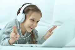 Niña sonriente con el ordenador portátil Imagenes de archivo