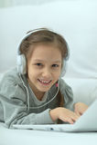 Niña sonriente con el ordenador portátil Imagen de archivo libre de regalías