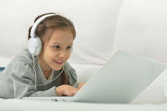 Niña sonriente con el ordenador portátil Fotografía de archivo libre de regalías