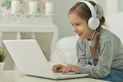 Niña sonriente con el ordenador portátil Imágenes de archivo libres de regalías