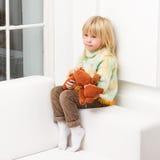 Niña sonriente con el oso de peluche que se sienta en hogar del sofá Imagenes de archivo