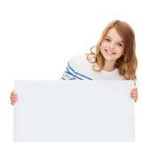 Niña sonriente con el tablero blanco en blanco Fotografía de archivo