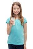 Niña sonriente con el vidrio de leche Foto de archivo