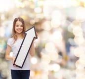 Niña sonriente con la flecha en blanco que destaca Imágenes de archivo libres de regalías