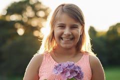 Niña sonriente con las flores que se colocan afuera por la tarde Fotos de archivo libres de regalías