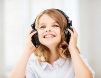 Niña sonriente con los auriculares en casa Fotos de archivo libres de regalías
