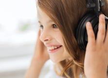 Niña sonriente con los auriculares en casa Foto de archivo libre de regalías