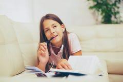 Niña sonriente con los auriculares en casa imagen de archivo