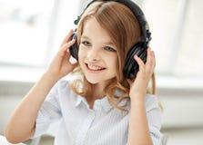Niña sonriente con los auriculares en casa Imagenes de archivo