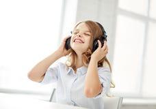 Niña sonriente con los auriculares en casa Imágenes de archivo libres de regalías