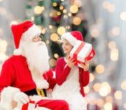 Niña sonriente con Papá Noel y los regalos Fotografía de archivo
