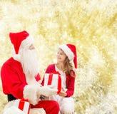 Niña sonriente con Papá Noel y los regalos Imágenes de archivo libres de regalías