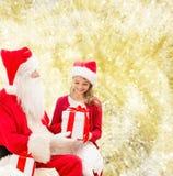Niña sonriente con Papá Noel y los regalos Imagenes de archivo
