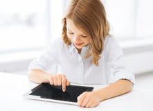 Niña sonriente con PC de la tableta en la escuela Foto de archivo libre de regalías