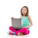 Niña sonriente con un ordenador portátil imagen de archivo