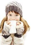Niña sonriente con una taza blanca de bebida caliente Imagen de archivo libre de regalías