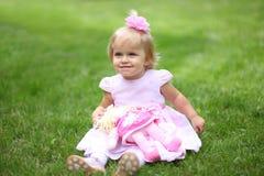 Niña sonriente dulce con el pelo rubio largo, sentándose en hierba en parque del verano, retrato al aire libre del primer Fotografía de archivo libre de regalías