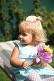 Niña sonriente dulce con el pelo rubio largo, sentándose en hierba en parque del verano, retrato al aire libre del primer Foto de archivo