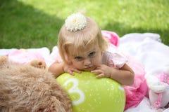 Niña sonriente dulce con el pelo rubio largo, sentándose en hierba en parque del verano, retrato al aire libre del primer Imagen de archivo libre de regalías