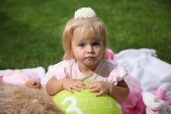 Niña sonriente dulce con el pelo rubio largo, sentándose en hierba en parque del verano, retrato al aire libre del primer Imagen de archivo