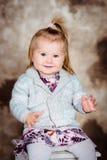 Niña sonriente dulce con el pelo rubio que se sienta en silla Foto de archivo libre de regalías