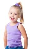 Niña sonriente en camiseta y pantalones vaqueros púrpuras Imagen de archivo libre de regalías