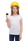 Niña sonriente en casco con el rodillo de pintura Imágenes de archivo libres de regalías