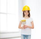Niña sonriente en casco con el rodillo de pintura Imagen de archivo libre de regalías