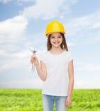 Niña sonriente en el casco de protección con la llave Imagen de archivo