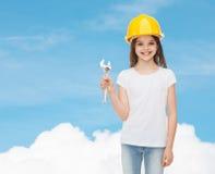 Niña sonriente en el casco de protección con la llave Fotografía de archivo libre de regalías